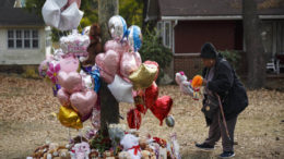 Chattanooga Resident Michelle Ingram places a teddy bear at a memorial to the six elementary school children killed this week in a fatal bus crash (Chattanooga Times-Free Press).