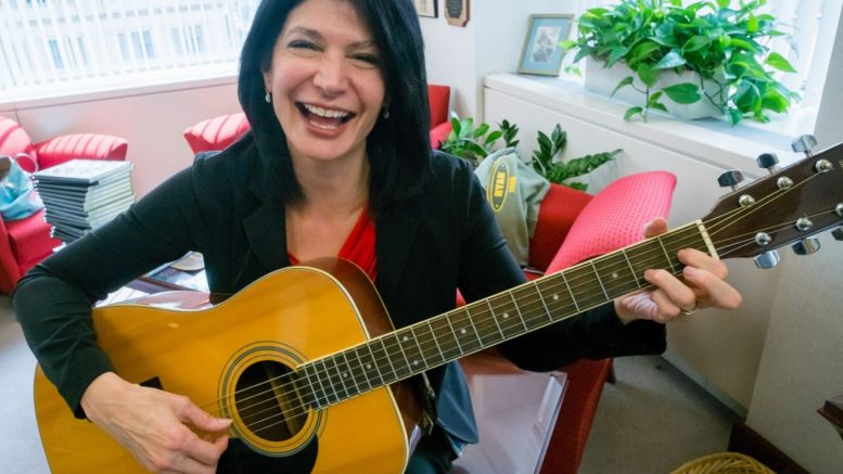 In this photo taken Sept. 19, 2014, National Education Association (NEA) President Lily Eskelsen Garcia poses with her guitar after an interview with The Associated Press in her office at NEA headquarters in Washington. (AP Photo/J. David Ake)